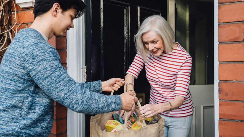 Teenage boy is delivering some groceries to an elderly woman.