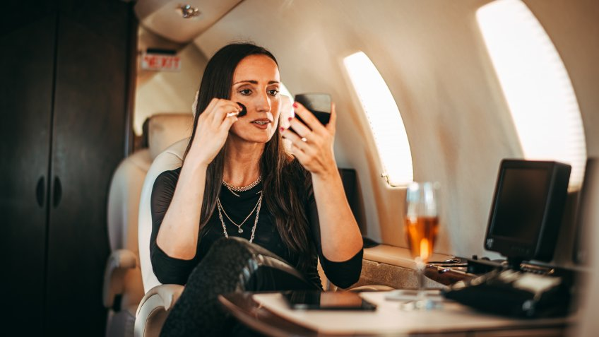 Rich and successful female putting her mascara on while traveling on a private airplane.