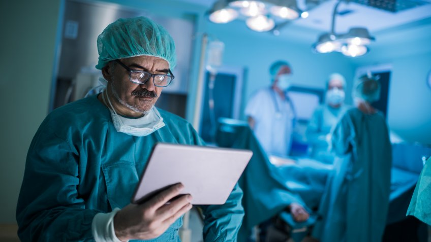 Mature doctor reading something from an e-reader in operating room.