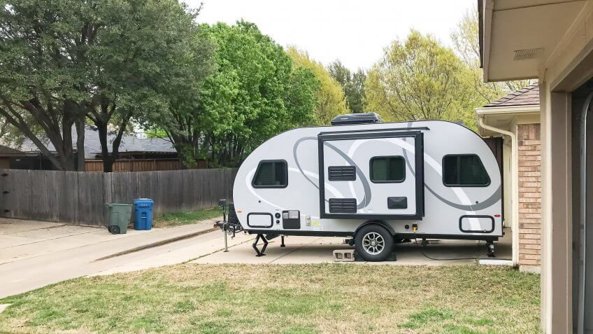 Side view of RV trailer parked at house garage backyard.