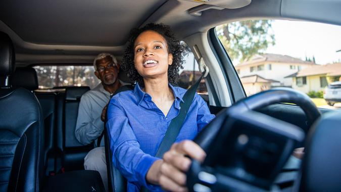 A young black woman drives a passenger in her car as a professional driver.