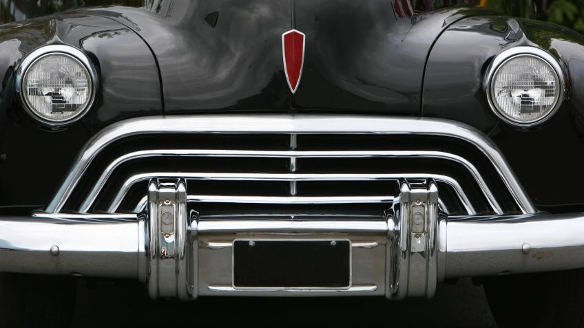 photograph of an old classic car in mint condition, shining chrome and highly polished finish , almost like a face with mouth eyes and nose.
