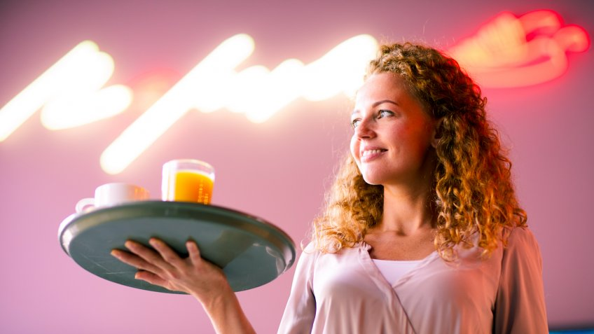 Cheerful attractive curly-haired waitress holding tray and looking aside while working at night bar - Image.