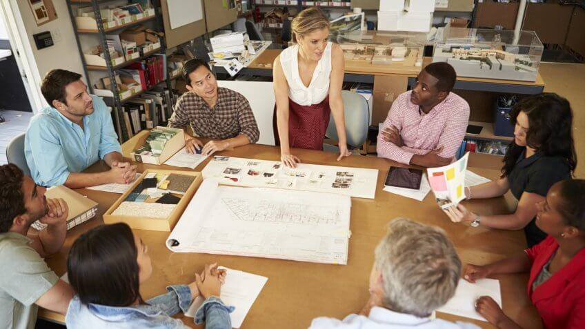 Female Boss Leading Meeting Of Architects Sitting At Table - Image.