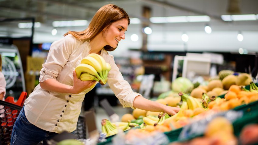 Young woman in the supermarket picking up bananas.