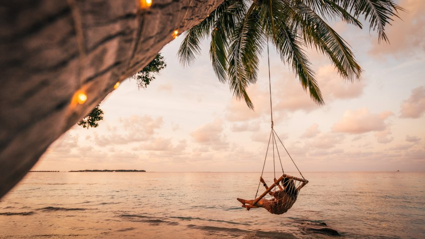 Young adult woman relaxing on a swing in a tropical paradise.