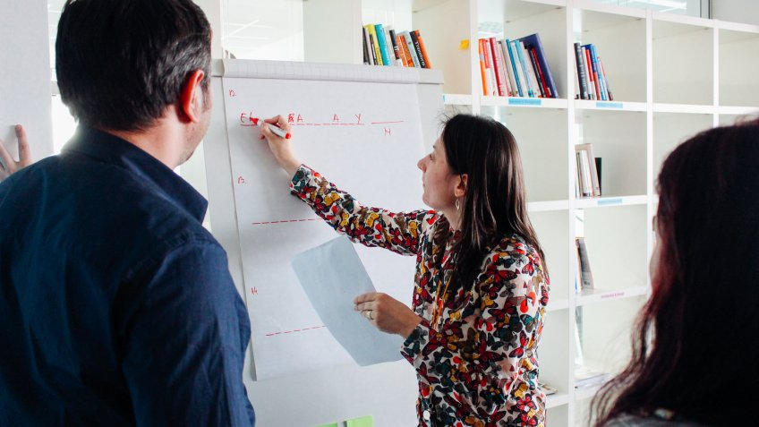 woman writing on board in start up office