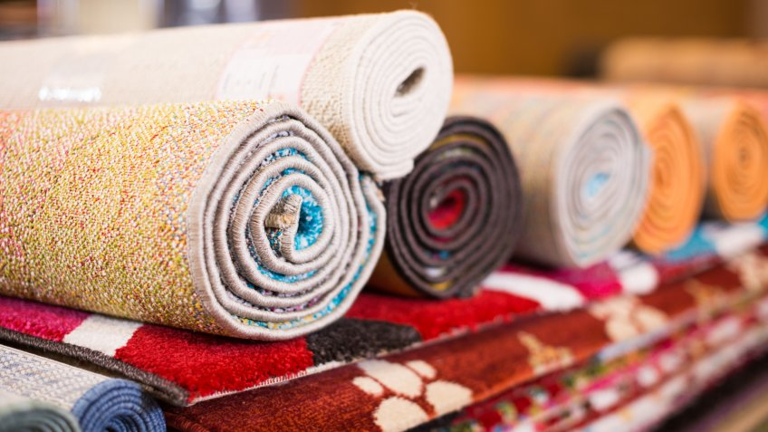 Stack of traditional  colorful carpets in carpet shop, nobody.