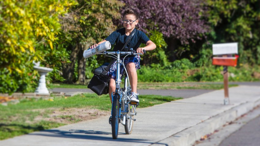 A young boy delivering newspapers on his bicycle - Image.