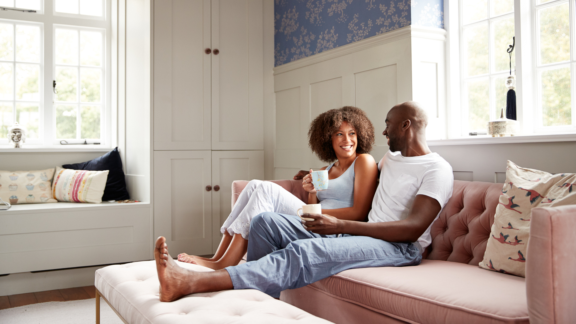 Young black couple sitting together on couch in living room drinking coffee and talking in the morning, low angle, full length.