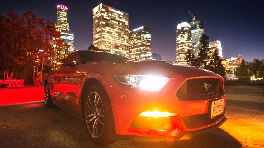Los Angeles, California, USA - March 22, 2016: Front view of a red Ford Mustang GT car parked on the street against the Los Angeles city downtown.
