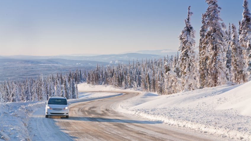 Car driving on an Icy Winter Road in Alaska's  Arctic Wilderness.