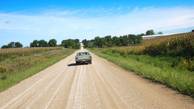 An old car going down a country road in rural Warren County, Iowa.