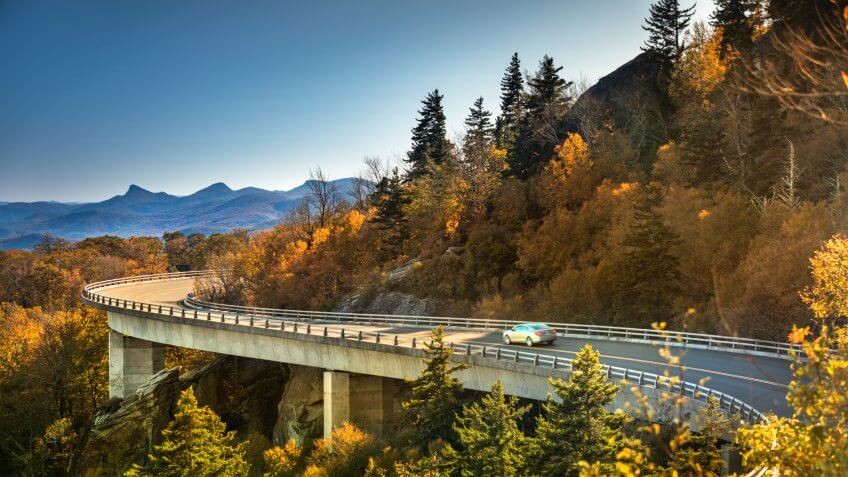 Cars travel on the Linn Cove Viaduct highway road on the Grandfather Mountain along the Blue Ridge Parkway in autumn North Carolina USA.
