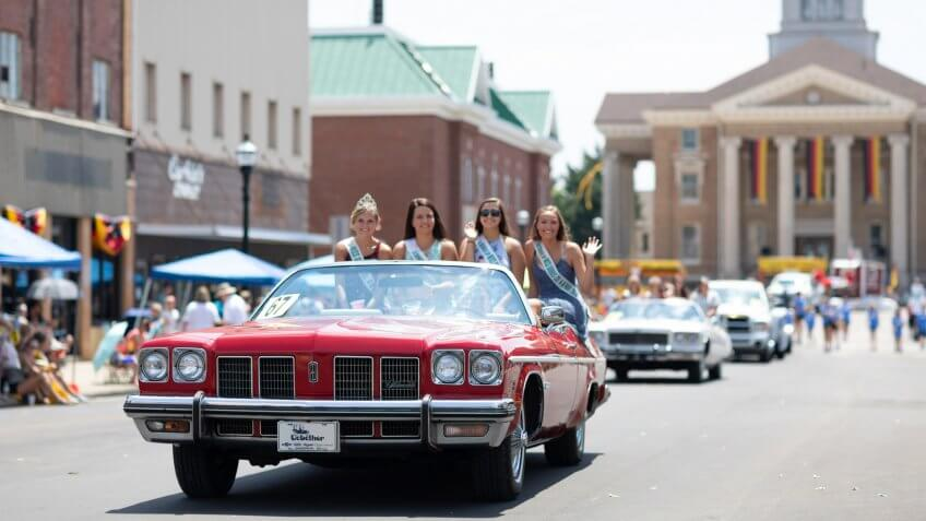Jasper, Indiana, USA - August 5, 2018: The Strassenfest Parade, A group of Beauty queens, riding on the back of a classic car during the parade.