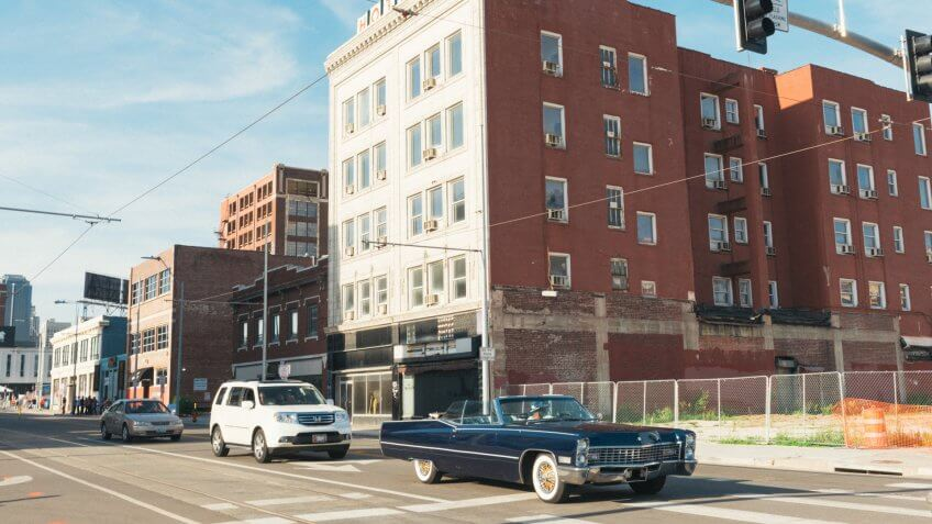 Kansas City, United States - May 6, 2016: On Friday afternoon a classic, blue Cadillac convertible car drives downtown past the traditional Midwestern American buildings.