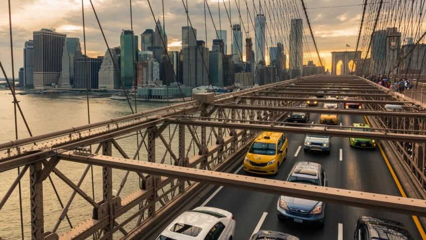 Traffic on Brooklyn Bridge at sunset with Manhattan skyline in the background (New York, USA).