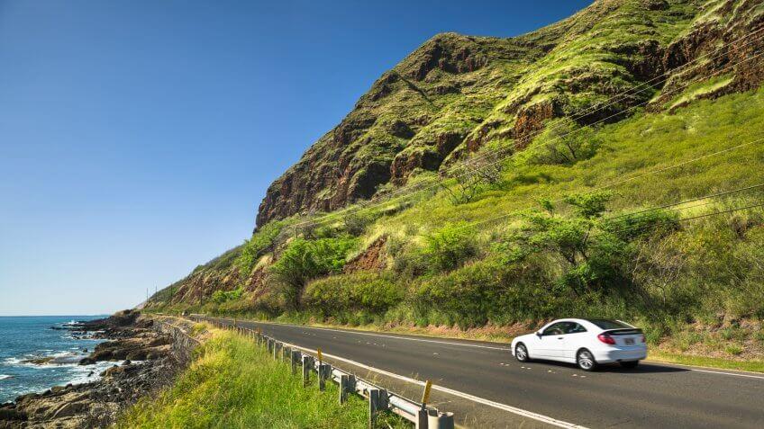 Haleiwa: Cars drive down the Farrington highway  by Kaena Point State Park and Keawaula beach in Oahu Hawaii USA.