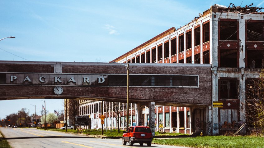 Detroit, Michigan, USA- April 24, 2016: A car passing by the famous abandoned Packard plant in Detroit.