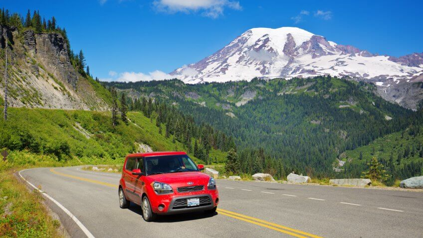 Mount Rainier National Park, Washington, USA - July 31, 2016: Visitors to Mount Rainier National Park touring the park along the scenic highway in their vehicle with Mount Rainier in the distance background.