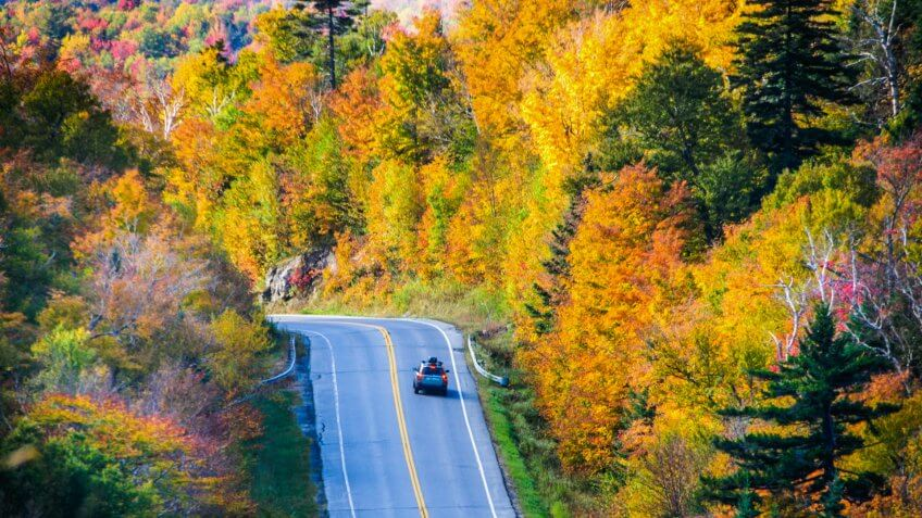 An automobile applies its brakes as it approches a sharp curve on the roadway through Camel's Hump State Forest (Rte.