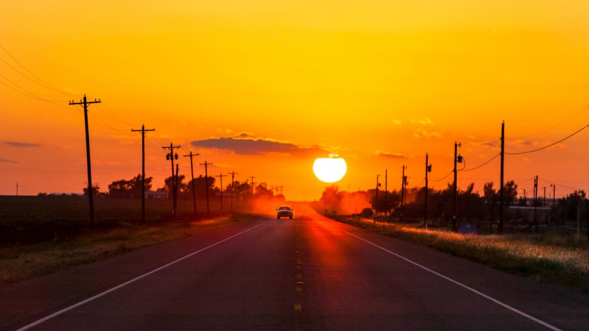 Pickup truck heading home at sunset on West Texas country road.