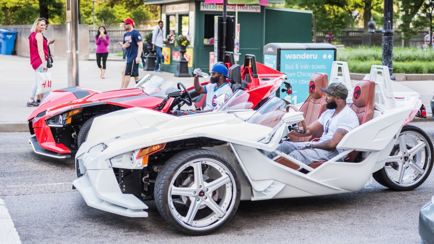 Chicago, USA - May 30, 2016: Two men with cubs shirt in flashy red and white Polaris Slingshot Ferrari sports cars on downtown street.