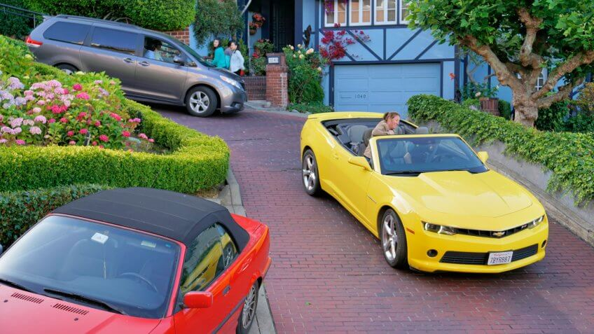 San Francisco, USA - May 29, 2014: Pedestrians and people in cars on the steep and winding Lombard Street in California, a popular tourist spot.