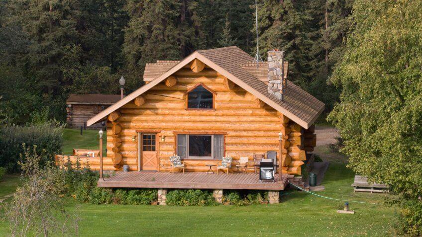 A log home alongside a river in Alaska - Image.