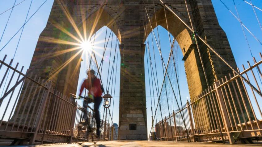 Scene of stop motion bicycle with Brooklyn bridge when sunrise, USA downtown skyline, Architecture and building with tourist concept.