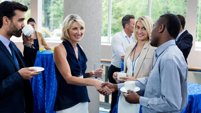 Business executives interacting with each other while having coffee at conference center.
