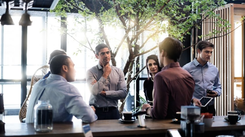 Businessman discussing with colleagues at office cafeteria.