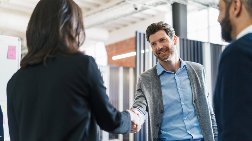 Businessman greeting female colleague at workplace.