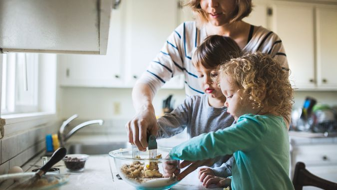 A happy young family prepares to bake chocolate chip cookies together, a boy and a girl about toddler age helping mix and stir the ingredients.