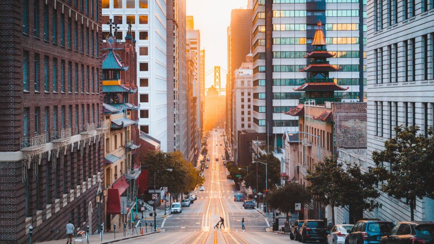 Beautiful view of downtown San Francisco with famous California Street illuminated in first golden morning light at sunrise in summer, San Francisco, California, USA.