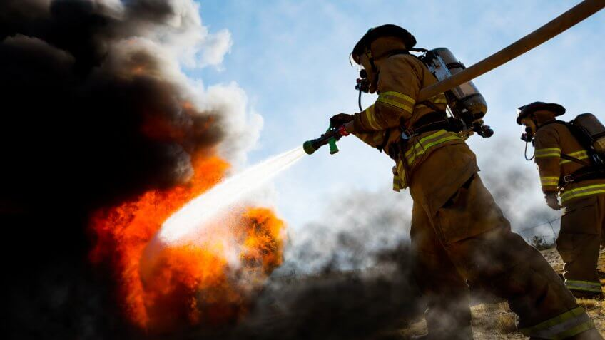Firefighters in a fire protection suit wearing firefighter helmet with breathing device and holding fire hose is extinguishing a burning house fire that is putting off excessive heat and smoke.