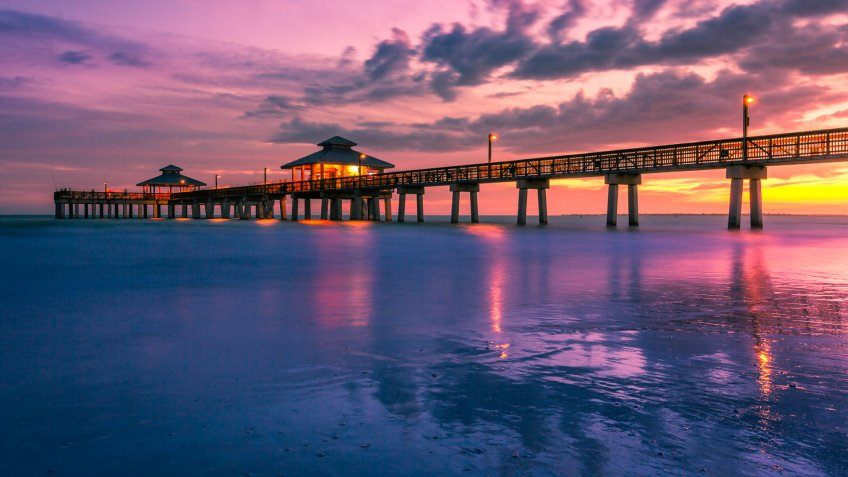 A colorful golden and purple sunset falls beneath the horizon at the Fort Myers Beach Pier in Florida, USA.