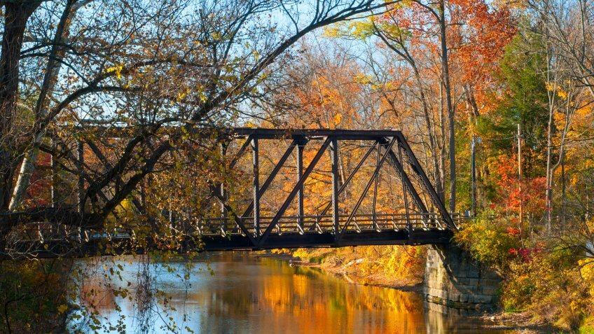An old pedestrian bridge over an autumn-hued stream - Image.