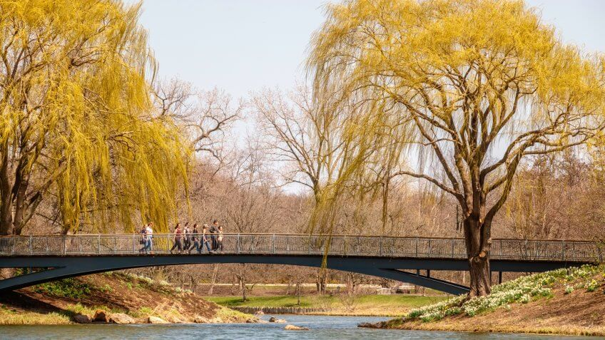 GLENCOE, ILLINOIS/USA - MAY 1, 2018: Seven women and one man stroll as a group, perhaps, along a footbridge across a lagoon on a sunny afternoon in spring at Chicago Botanic Garden.