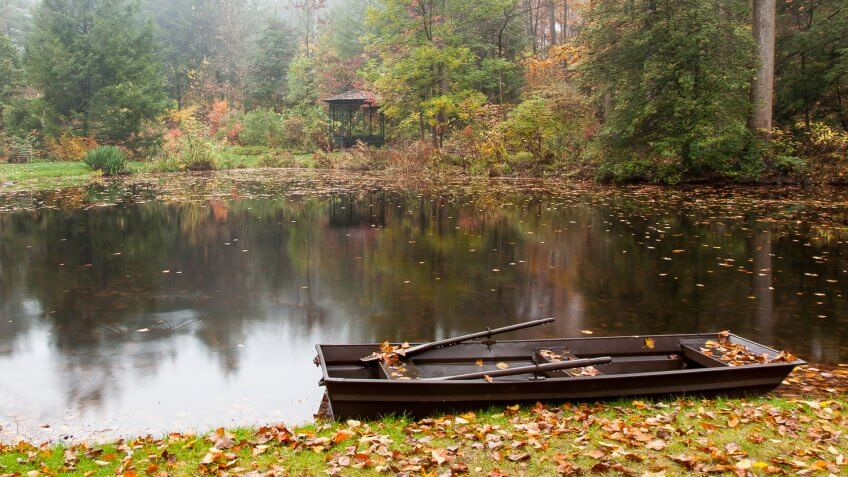 Tranquil view of a rowboat, pond and gazebo in autumn.