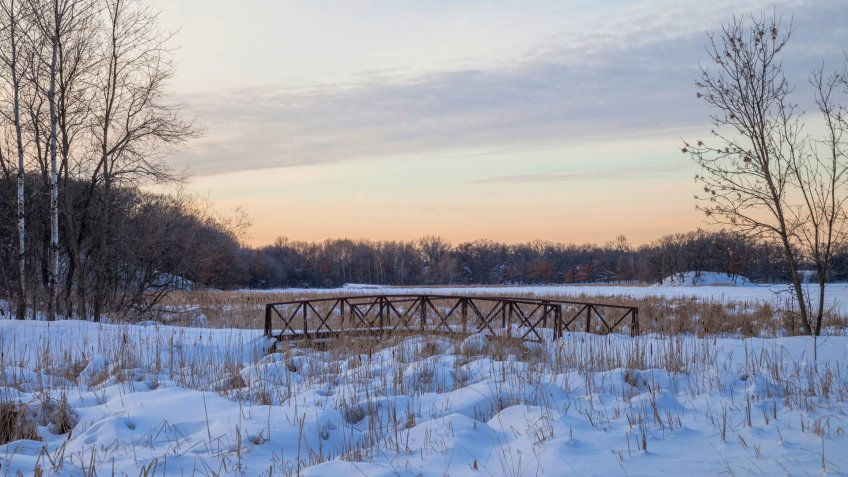 A Medium Shot of a Walking Bridge in a Snowy Suburban Minnesota Landscape during a Winter Golden Hour - Image.