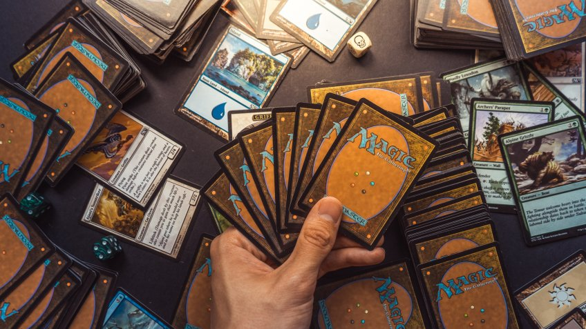 Bratislava/Slovakia - 06/13/2018: Magic the Gathering card playing game background with hand holding cards and cards and dice spread out behind - Image.