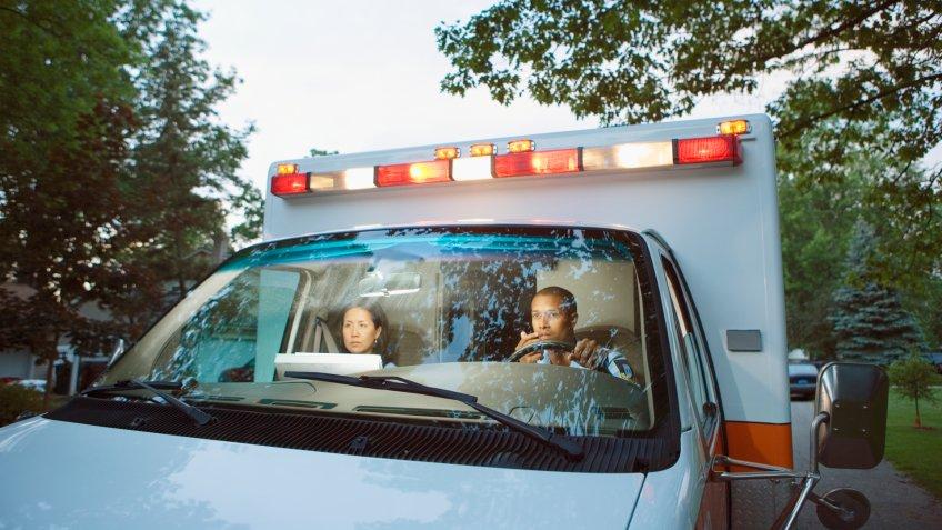 Male and female paramedics in cab of ambulance.