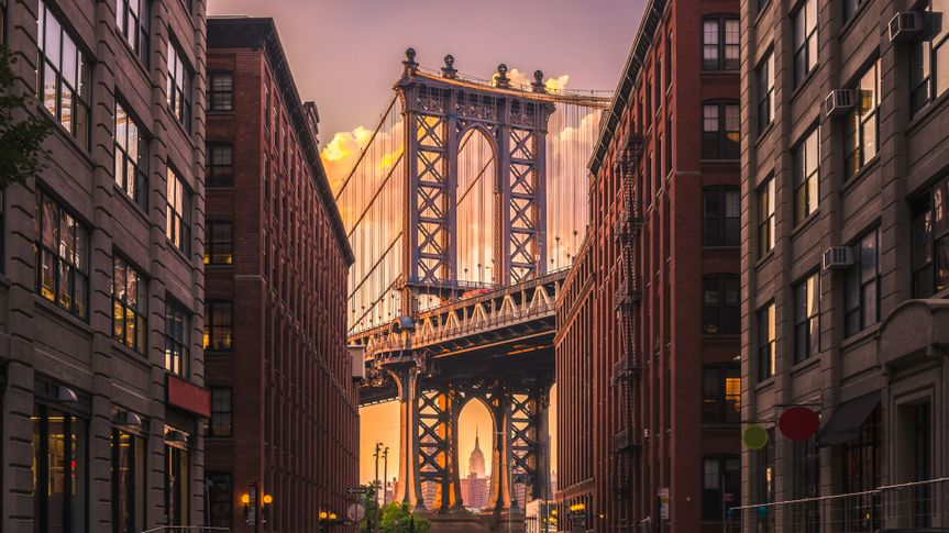 Manhattan bridge seen from a brick buildings in Brooklyn street in perspective, New York, USA.