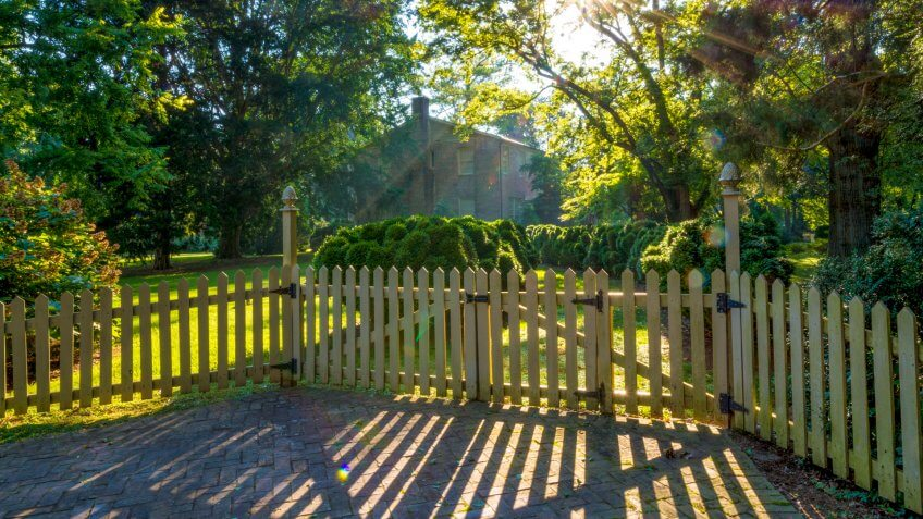 Small town neighborhood with trees and fence surrounding house - Image.