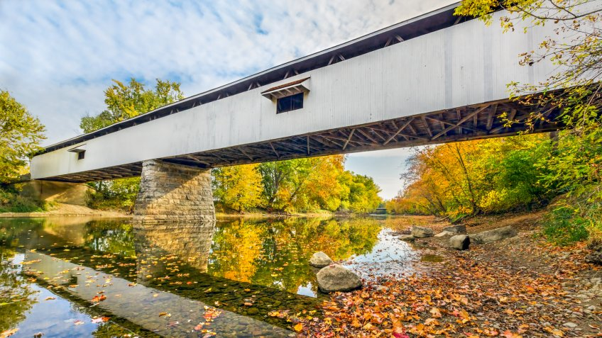 Potter's Covered Bridge crosses the West Fork of the White River surrounded by colorful fall foliage in Noblesville, Indiana.