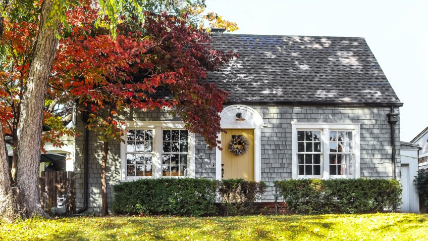 Beautiful grey wood shingle cottage with autumn trees and wreath on door - Image.