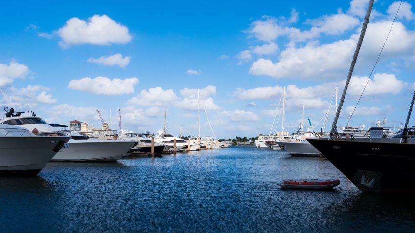 Yachts and sailboats docked at palm harbor marina on a sunny day.