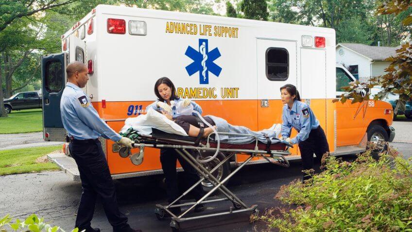 Paramedics putting woman into ambulance.