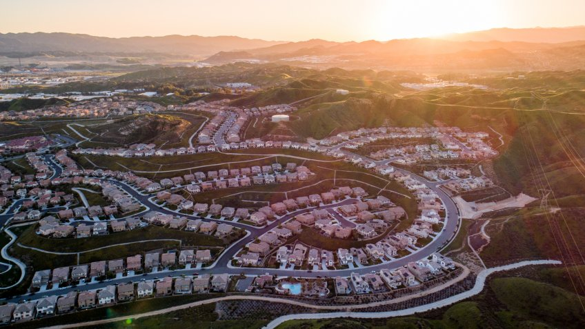 Aerial of tract housing and American suburban development in Southern California at sunset.